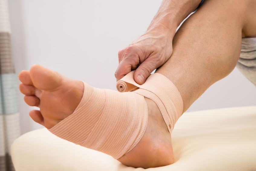 40579815 - close-up of a man putting elastic bandage on his injured foot